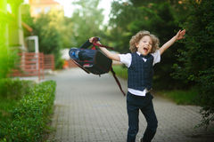 The schoolboy angrily swings his backpack in the school yard. Royalty Free Stock Images