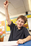 Schoolboy Answering Question In Classroom Stock Photos
