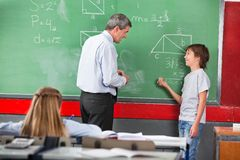 Schoolboy Asking Question To Teacher While Solving Stock Images