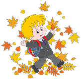 Schoolboy with autumn leaves. Joyful schoolboy throws up colorful leaves Royalty Free Stock Photo