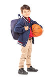 Schoolboy with backpack holding a basketball Stock Photography
