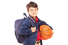 Schoolboy with backpack holding a basketball Stock Image
