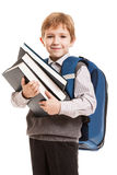 Schoolboy with backpack holding books. Little smiling boy with school backpack holding education books in hands Royalty Free Stock Images