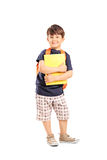 Schoolboy with backpack holding a notebook. Isolated on white background Stock Photos