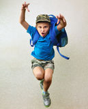 Schoolboy with backpack jumping and running Royalty Free Stock Photo