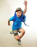 Schoolboy with backpack jumping and running Royalty Free Stock Image