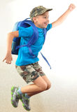 Schoolboy with backpack jumping and running Stock Photography
