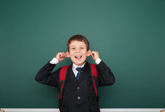 Schoolboy with backpack on school board background Stock Image
