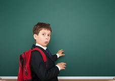 Schoolboy with backpack on school board background Stock Photography