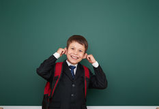Schoolboy with backpack on school board background Stock Photo