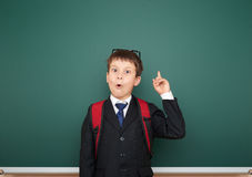 Schoolboy with backpack on school board background Stock Photos