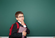Schoolboy with backpack on school board background Stock Images