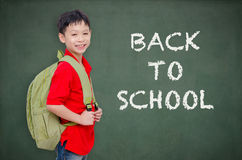 Schoolboy with backpack standing in front of chalkboard Stock Photography