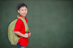 Schoolboy with backpack standing in front of chalkboard Stock Image