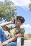 Schoolboy on bench taking break using mobile Royalty Free Stock Photo