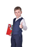Schoolboy in blue suit with book in his hand thumbs up royalty free stock photos