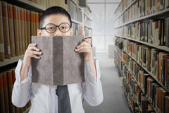 Schoolboy with book in the library aisle. Portrait of a schoolboy covering his face with a book in the library aisle Stock Photo