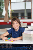 Schoolboy With Books And Globe At Desk Stock Image