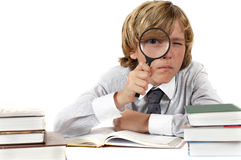 Schoolboy with books and magnifying glass Stock Photos