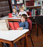 Schoolboy With Books Sitting At Library Stock Photo