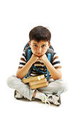Schoolboy bored, frustrated and overwhelmed by studying homework. Little boy sitting down on floor Royalty Free Stock Photography