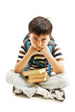 Schoolboy bored, frustrated and overwhelmed by studying homework. Little boy sitting down on floor. On white background Royalty Free Stock Photo