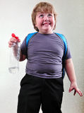 Schoolboy with a bottle of water making faces Royalty Free Stock Photo