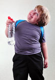 Schoolboy with a bottle of water making faces Stock Photography