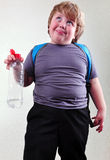 Schoolboy with a bottle of water making faces. Portrait of funny cute blond schoolboy with a bottle of water making faces Royalty Free Stock Photo
