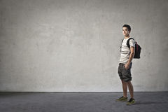 Schoolboy. Boy in casual dress with his hand in his pocket with a backpack Stock Image