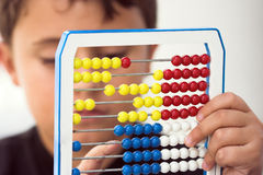Schoolboy calculate with abacus. Shallow dof Stock Image