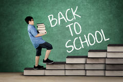 Schoolboy carrying pile of books on stair. Picture of schoolboy carrying pile of books while stepping on books stair with back to school word chalkboard Stock Image