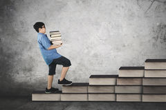Schoolboy carrying pile of books on staircase Stock Image