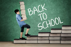 Schoolboy carrying stack of books on stair. Image of schoolboy carrying stack of books while walking on books stair with back to school word on chalkboard Royalty Free Stock Photography