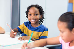 Schoolboy with classmate writing on book Royalty Free Stock Photos