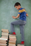 Schoolboy climbing steps of books stack Stock Image