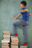 Schoolboy climbing steps of books stack Stock Photography