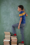 Schoolboy climbing steps of books stack Stock Images
