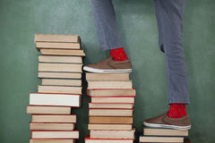 Schoolboy climbing steps of books stack against chalkboard Royalty Free Stock Image