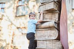 Schoolboy climbs the levels of knowledge from books. School lessons. Back to school.  royalty free stock images