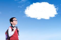 Schoolboy with cloud on the sky. Male elementary school student carrying bag while wearing uniform and looking at white cloud on the sky Royalty Free Stock Photography