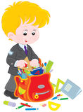 Schoolboy competing his schoolbag. Elementary school student putting rules, textbooks, exercise books and pencils into his school bag Stock Photo