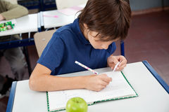 Schoolboy Copying From Cheat Sheet During. High angle view of little boy copying from cheat sheet at desk during examination royalty free stock photo
