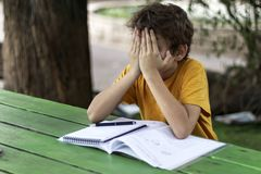 The schoolboy covered his face with his hands. On the wooden desk an open notebook with homework Royalty Free Stock Photography