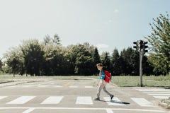 Schoolboy crossing road royalty free stock image