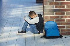 Schoolboy crying in the hallway of the school. Negative emotion Royalty Free Stock Photos