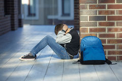 Schoolboy crying in the hallway of the school. Negative emotion stock photos