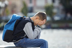 Schoolboy crying on the street. Negative emotion stock image