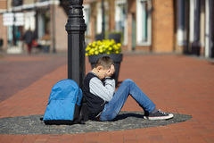 Schoolboy crying on the street Stock Photography