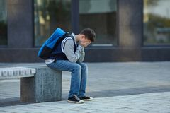 Schoolboy crying in the yard of the school stock photos